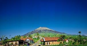 Montagne et village avec le ciel bleu clair Photos libres de droits