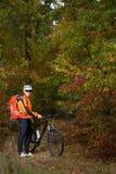 Montagne faisant du vélo en bas du journal Touriste avec le voyage de sac à dos sur le vélo Image stock