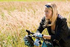 Montagne faisant du vélo les prés ensoleillés folâtres de jeune femme Photo stock