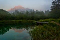Montagne illuminate alba che riflettono nel lago della foresta Immagine Stock