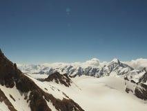 Montagne innevate irregolari che aumentano su sopra le nuvole spesse all'alba, Caucaso, Cabardino-Balcaria, regione di Bezengi Fotografie Stock Libere da Diritti