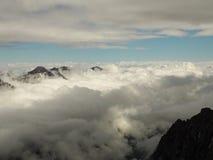 Montagne innevate irregolari che aumentano su sopra le nuvole spesse all'alba, Caucaso, Cabardino-Balcaria, regione di Bezengi Immagini Stock Libere da Diritti