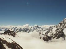 Montagne innevate irregolari che aumentano su sopra le nuvole spesse all'alba, Caucaso, Cabardino-Balcaria, regione di Bezengi Fotografie Stock