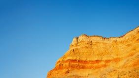 Montagne jaune sur un fond de ciel bleu Images stock