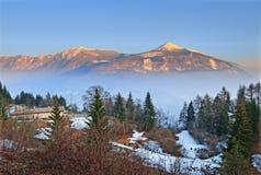 Montagne nebbiose all'indicatore luminoso di tramonto Immagini Stock Libere da Diritti