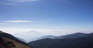Montagne nebbiose e cielo blu Fotografia Stock Libera da Diritti