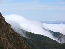 Montagne nebbiose sotto un cielo blu Immagine Stock