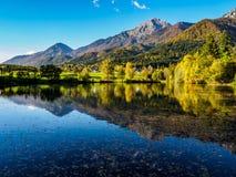 Montagne nei colori di autunno che riflettono il lago Fotografie Stock