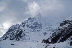 Montagne nella nebbia coperta di neve e di foresta di inverno vicino a Mont Blanc Alpes, Italia Immagini Stock
