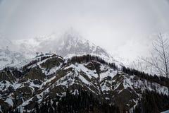 Montagne nella nebbia coperta di neve e di foresta di inverno vicino a Mont Blanc Alpes, Italia Fotografie Stock
