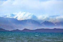 Montagne nelle nuvole vicino al lago fotografie stock