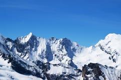 Montagne nevose di inverno e bello cielo blu nel giorno freddo del sole Fotografia Stock Libera da Diritti