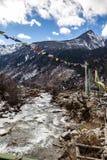 Montagne noire avec la neige sur le dessus Au sol est la rivière congelée avec la pierre, la glace, l'herbe jaune et des drapeaux Photo stock