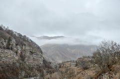 Montagne, nuvole, alberi e case fotografia stock libera da diritti