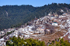 Montagne ricoperte neve e un villaggio Immagine Stock Libera da Diritti