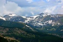 Montagne ricoperte neve sopra la linea di albero in una foresta del pino Immagine Stock