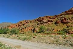 Montagne rocciose rosse vicino alla città di Tamasha Immagine Stock
