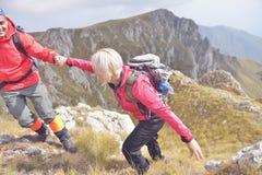 Montagne s'élevante de aide de femme de jeune homme photo stock