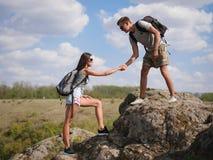 Montagne s'élevante de aide de femme de jeune homme Style de vie sain Images stock