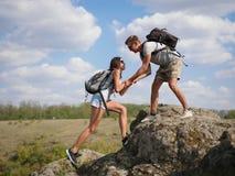 Montagne s'élevante de aide de femme de jeune homme Style de vie sain Photo stock