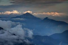 Montagne scure, foschia di autunno e nuvole soleggiate in alpi slovene Fotografie Stock