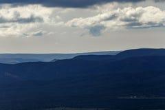 Montagne sopra le montagne un giorno nuvoloso Immagini Stock