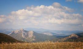Montagne sotto il cielo blu con le nuvole Immagine Stock