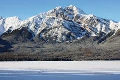 Montagne sous un ciel bleu derrière un lac figé Image stock