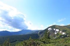 Montagne stupefacenti delle alpi nella stagione estiva con le nuvole nel fondo Immagine Stock