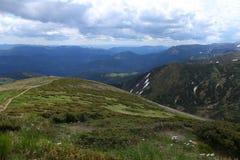 Montagne stupefacenti verdi delle alpi nella stagione estiva con le nuvole nel fondo Immagine Stock