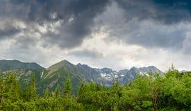Montagne sui precedenti del cielo con le nuvole di tempesta Fotografia Stock Libera da Diritti