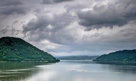 Montagne, un grande fiume e un cielo con molte nuvole nere fotografie stock libere da diritti