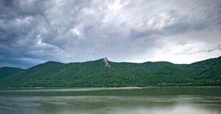 Montagne, un grande fiume e un cielo con molte nuvole nere immagini stock