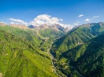 Montagne verdi con cielo blu e le nuvole, con il fiume e la foresta Immagini Stock