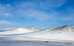 Montagnes à l'horaire d'hiver contre le ciel bleu Image stock