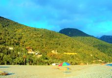 Montagnes bouclées vertes contre le ciel bleu et la plage avec des parapluies de plage Photo stock