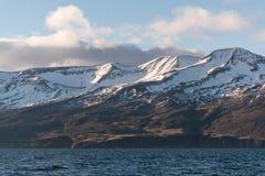 Montagnes couronnées de neige et mer Photos stock