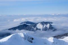 Montagnes couvertes de neige et de forêt au milieu des nuages Photo stock