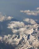 Montagnes couvertes par neige évidentes de la fenêtre d'avion Images stock