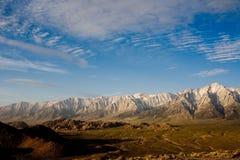 Montagnes couvertes par neige sous un ciel bleu Photo stock