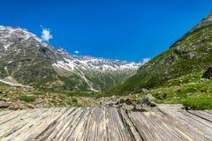 Montagnes d'Alpes d'un vieux pont en bois Photographie stock