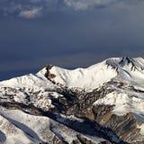 Montagnes d'hiver à la soirée du soleil et aux nuages foncés Photos libres de droits
