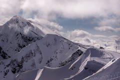 Montagnes d'hiver de matin avec des télésièges Image libre de droits