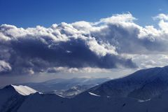 Montagnes d'hiver en nuages de soirée et de lumière du soleil Photo stock