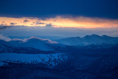 Montagnes d'hiver pendant le coucher du soleil Photographie stock libre de droits