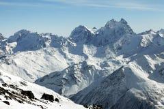 Montagnes dans la neige par temps nuageux Images stock