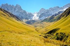 Montagnes de Caucase pendant l'été, l'herbe verte, le ciel bleu et la neige sur Chiukhebi maximal Image libre de droits