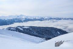 Montagnes de Caucasien principal Ridge couvert de neige et forêt et barrière en bois Photographie stock