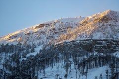 Montagnes de neige au coucher du soleil avec le brouillard Image stock