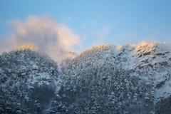 Montagnes de neige au coucher du soleil avec le brouillard Photographie stock